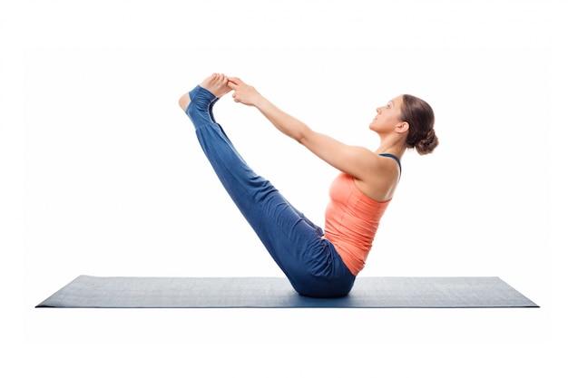 A mulher bonita desportiva do ajuste pratica o asana da ioga