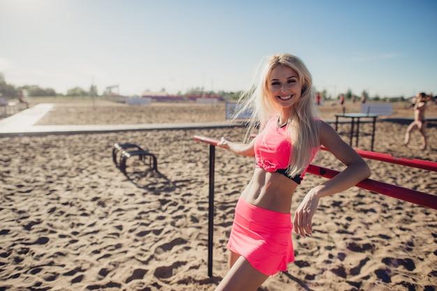 A mulher bonita do atleta da aptidão que descansa após dá certo exercitar na noite do verão da praia no retrato ao ar livre da luz do sol ensolarada.