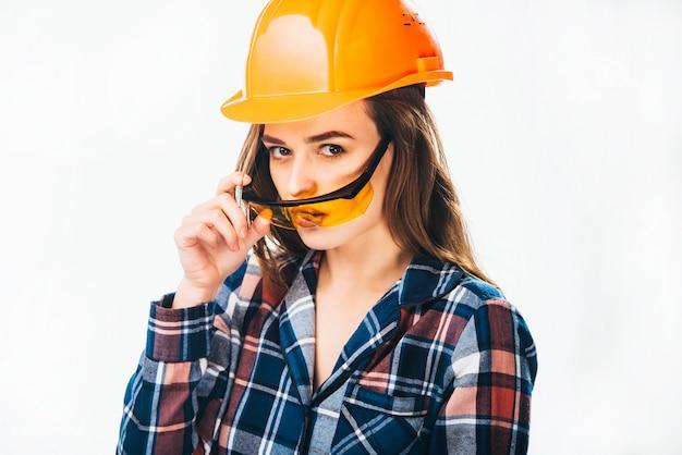 A mulher bonita do construtor que usa o capacete protetor alaranjado olha sobre óculos de segurança amarelos