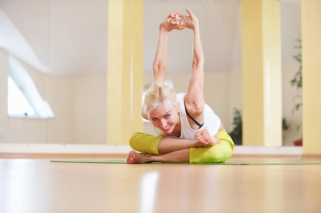 A mulher bonita do iogue do ajuste desportivo pratica asana da ioga adho mukha agni stambhasana na sala de fitness