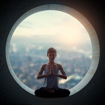 A mulher bonita do iogue do ajuste desportivo pratica o asana da ioga padmasana. pose de lótus em uma janela redonda