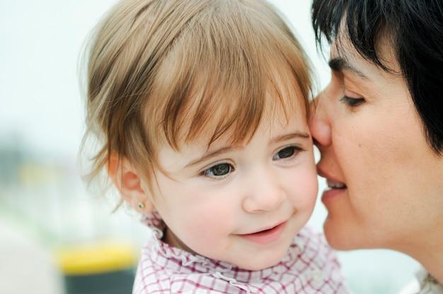 A mulher bonita e sua filha pequena estão abraçando