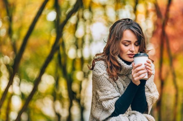 A mulher bonita em uma camiseta feita malha guarda um vidro do café quente no parque no outono.