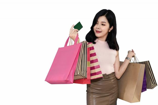 A mulher bonita está comprando na alameda usando o cartão de crédito vidros vestindo da mulher e forma guardar do saco de compras no armazém.