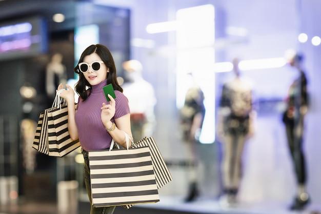 A mulher bonita está comprando na alameda vidros vestindo e chapéu da mulher que guardam a forma do saco de compras no armazém.