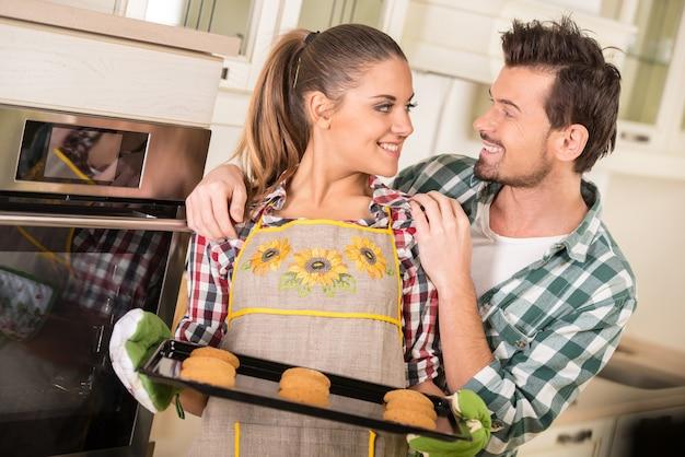A mulher bonita está guardando a panela quente com cookies.