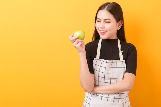 A mulher bonita está segurando a maçã em fundo amarelo