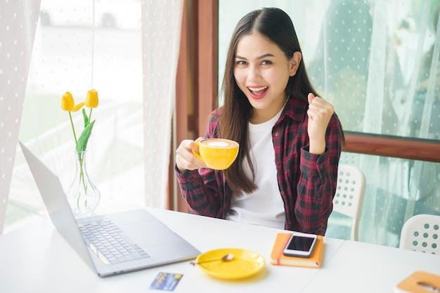 A mulher bonita está trabalhando com o computador portátil na cafeteria