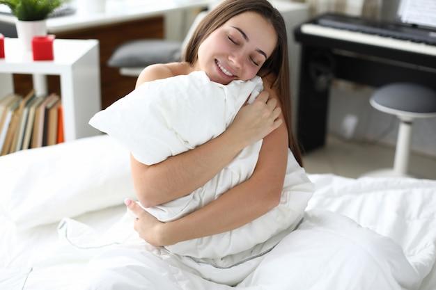 A mulher bonita feliz senta-se na cama e abraça o travesseiro branco.