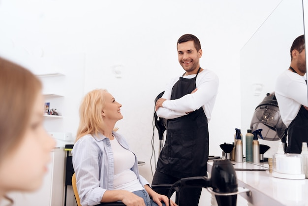 A mulher bonita madura está fazendo o penteado no salão de beleza.