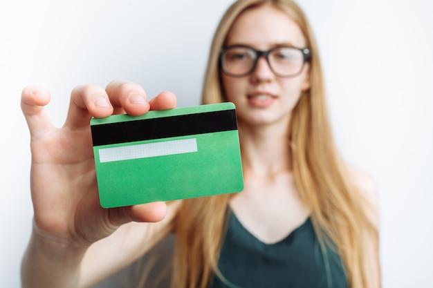 A mulher bonita mostra o cartão de crédito