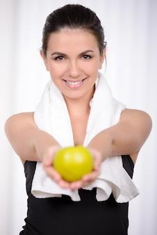 A mulher bonita no sportswear prende uma maçã.