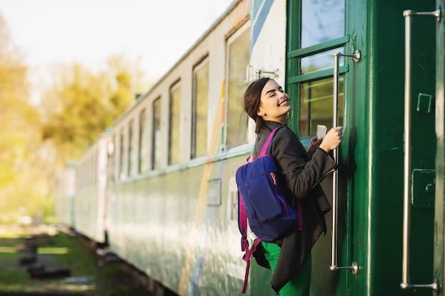 A mulher bonita nova com trouxa vai viajar pelo trem na estação de trem.