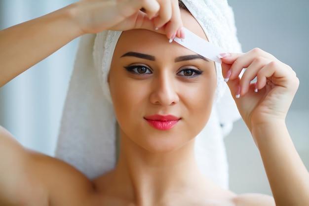 A mulher bonita nova faz as pálpebras da cera em seu banheiro.
