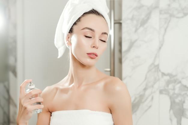 A mulher bonita nova pulveriza o perfume em seu pescoço envolvido nas toalhas no banheiro. maquiagem de beleza e conceito de cuidado de pele