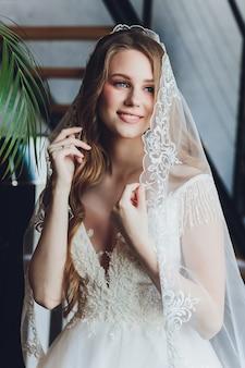 A mulher bonita posando em um vestido de noiva.