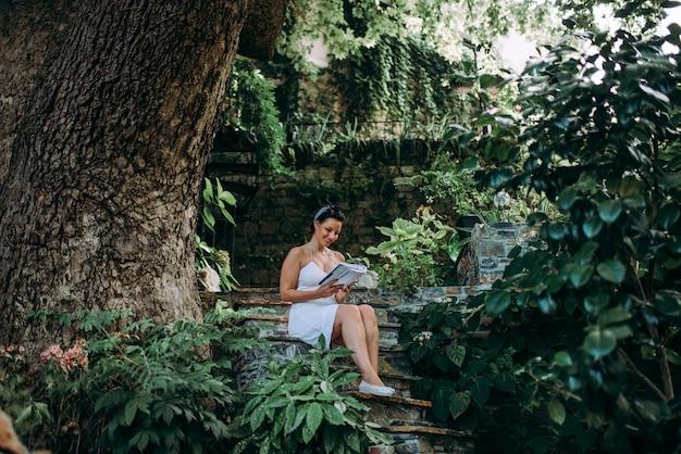 A mulher bonita que lê um livro no conto de fadas gosta do jardim.
