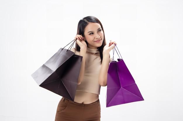 A mulher bonita segurando sacolas de compras na mão, com sorriso e sentimento feliz