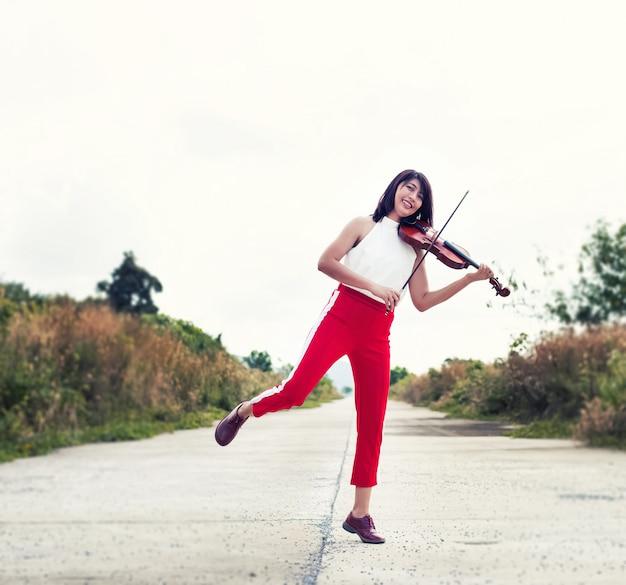 A mulher bonita tocando violino, com desfrutar e sentimento feliz, vista para o campo, luz embaçada ao redor