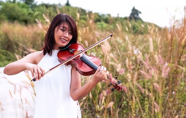 A mulher bonita tocando violino, com um sentimento feliz, posando de modelo de retrato, vista para o campo, luz embaçada ao redor