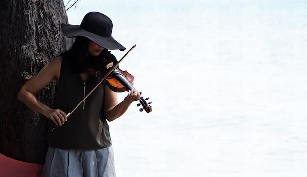 A mulher bonita tocando violino debaixo da árvore, para relaxar o tempo