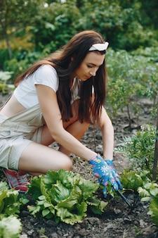 A mulher bonita trabalha em um jardim