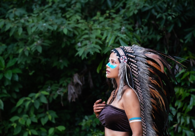 A mulher bonita vestindo cocar penas de pássaros.