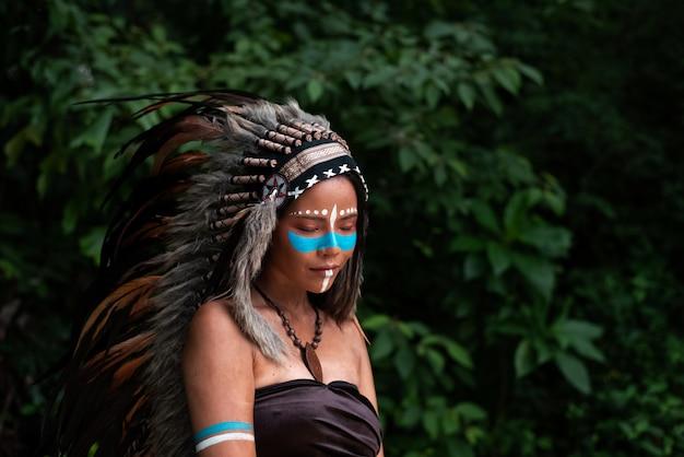 A mulher bonita vestindo penas de cocar de birds.paint corpo com cor marrom e rosto com cor azul, modelo posando na floresta