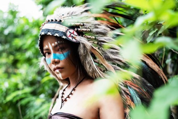 A mulher bonita vestindo penas de cocar de pássaros