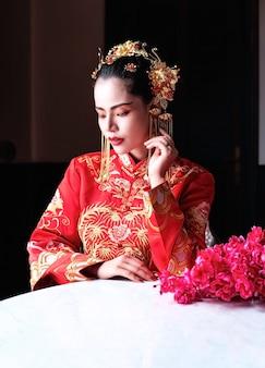 A mulher bonita vestindo terno vermelho, vire o rosto para baixo, olhando a mão dela, retrato de modelo posando no festival do ano novo chinês
