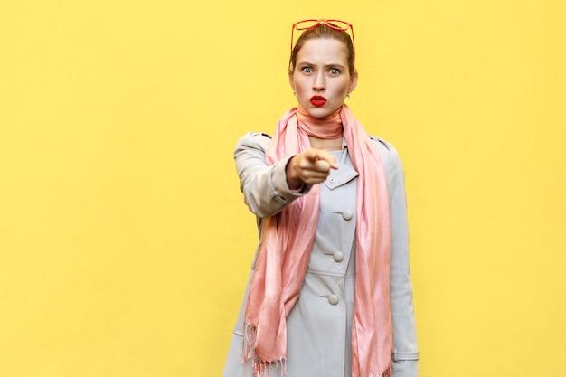 A mulher bonita, vestindo um casaco de outono, abrindo amplamente a boca, tendo olhares chocados e surpresos, apontando o dedo para a câmera. foto de estúdio, parede amarela