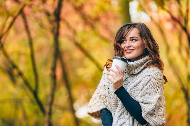 A mulher bonito com uma xícara de café sorri e olha afastado no parque no outono.