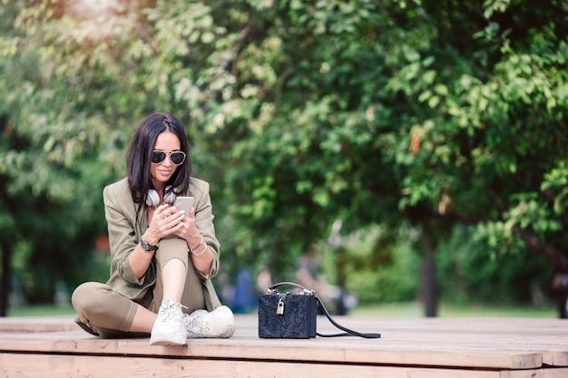 A mulher bonito está lendo a mensagem de texto no telefone celular ao sentar-se no parque.