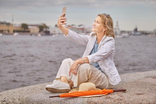 A mulher branca atraente sênior, com cerca de 60 anos, está sentada perto do rio, em um tecido casual e elegante, com o telefone celular nas mãos.