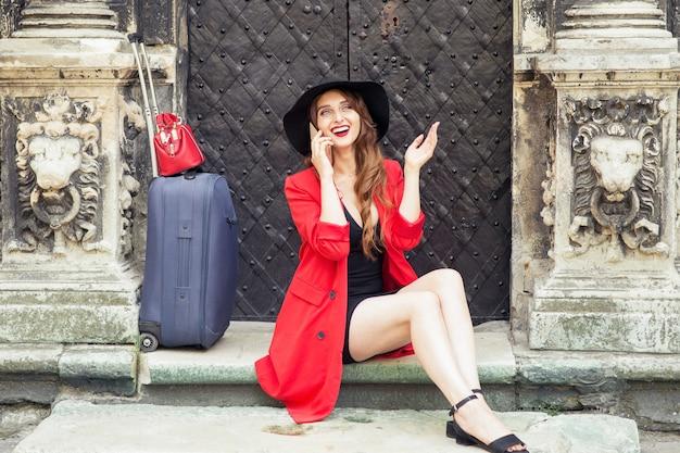 A mulher caucasiana sorridente com uma mala está falando pelo smartphone ao ar livre.