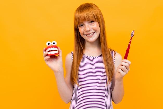 A mulher caucasiano bonita com cabelo vermelho sorri e recomenda escovas os dentes isolados no fundo amarelo