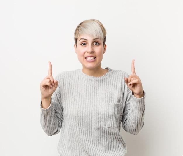 A mulher caucasiano curvilínea nova isolada no branco indica com os dois dedos dianteiros que mostram acima um espaço em branco.