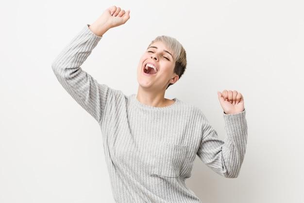A mulher caucasiano curvilínea nova isolada no fundo branco que comemora um dia especial, salta e levanta os braços com energia.