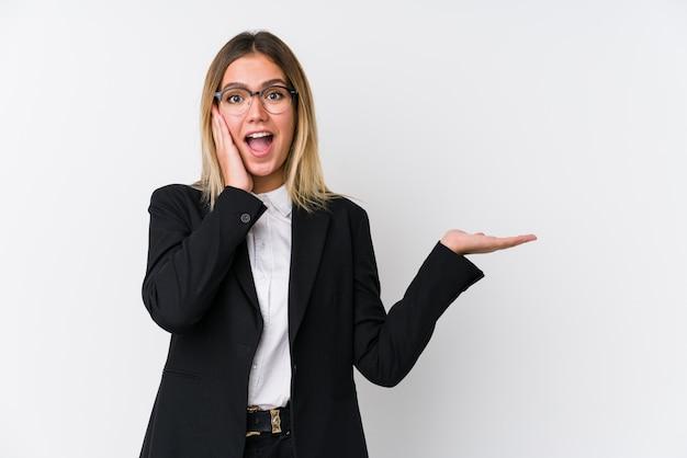 A mulher caucasiano do negócio novo prende o espaço da cópia em uma palma, mantém a mão sobre a bochecha. espantado e encantado.