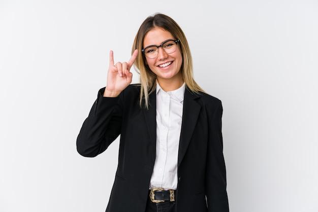 A mulher caucasiano do negócio novo que mostra chifres gesticula como um conceito da revolução.