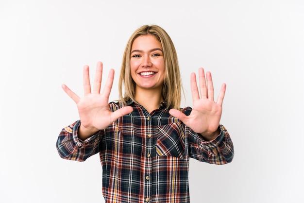 A mulher caucasiano loura nova isolou mostrar a tonelada do número com mãos.