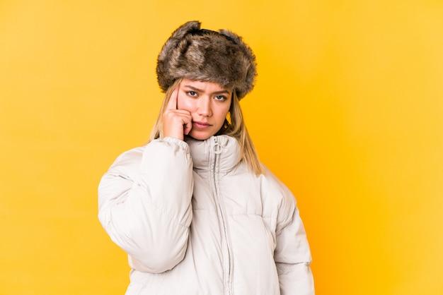 A mulher caucasiano loura nova que veste um inverno veste apontar o templo com o dedo, pensando, focalizado em uma tarefa.