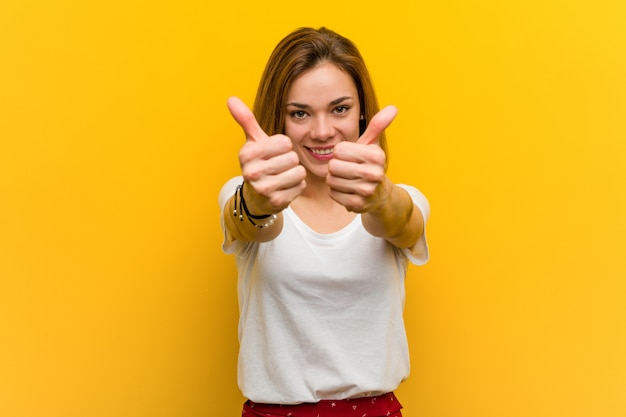 A mulher caucasiano natural nova com polegares levanta, elogios sobre algo, apoia e respeita o conceito.