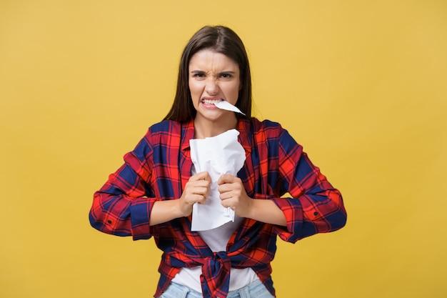 A mulher caucasiano nova agressiva rasga o contrato ou a folha de papel branca.