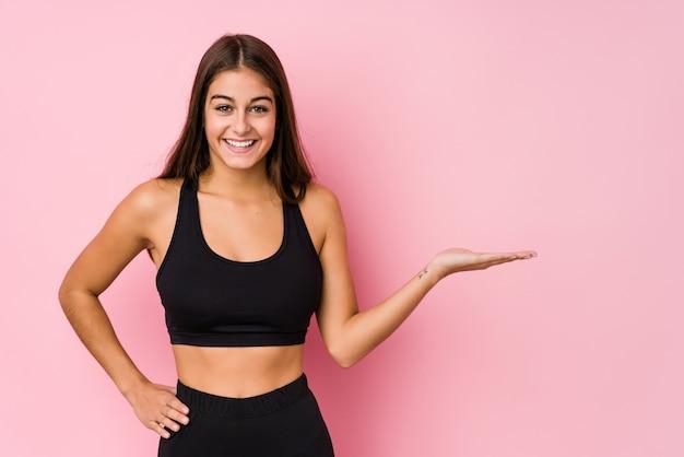 A mulher caucasiano nova da aptidão que faz o esporte isolou mostrando um espaço da cópia em uma palma e segurando uma outra mão na cintura.