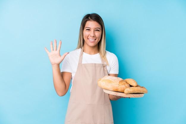 A mulher caucasiano nova do padeiro isolou o número mostrando alegre de sorriso cinco com dedos.
