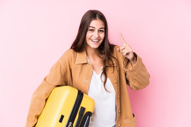 A mulher caucasiano nova do viajante que guarda uma mala de viagem isolou uma ideia, conceito da inspiração.