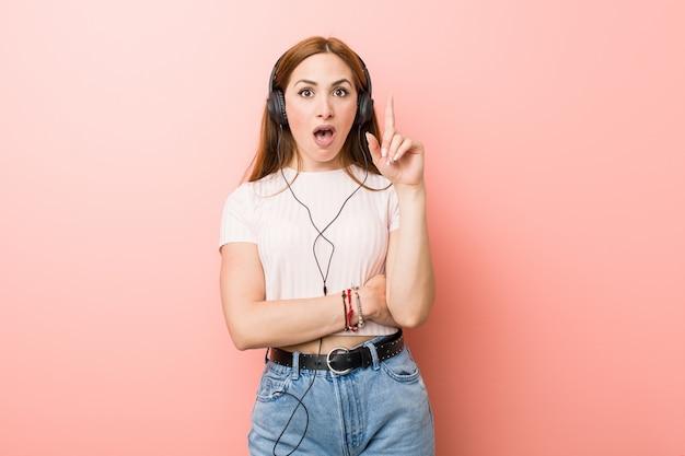 A mulher caucasiano nova escuta a música que tem alguma grande ideia, conceito da faculdade criadora.
