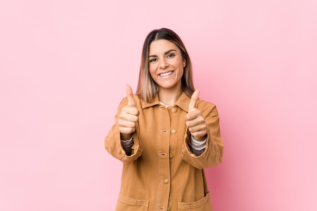 A mulher caucasiano nova isolada com polegares levanta, felicidades sobre algo, apoia e respeita o conceito.
