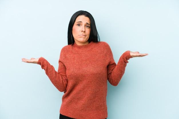 A mulher caucasiano nova isolada em um fundo azul confuso e duvidoso encolhe os ombros para guardar um espaço da cópia.
